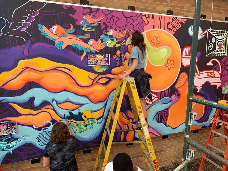 Two women painting a mural. One in standing on a ladder and the other is standing on the ground painting
