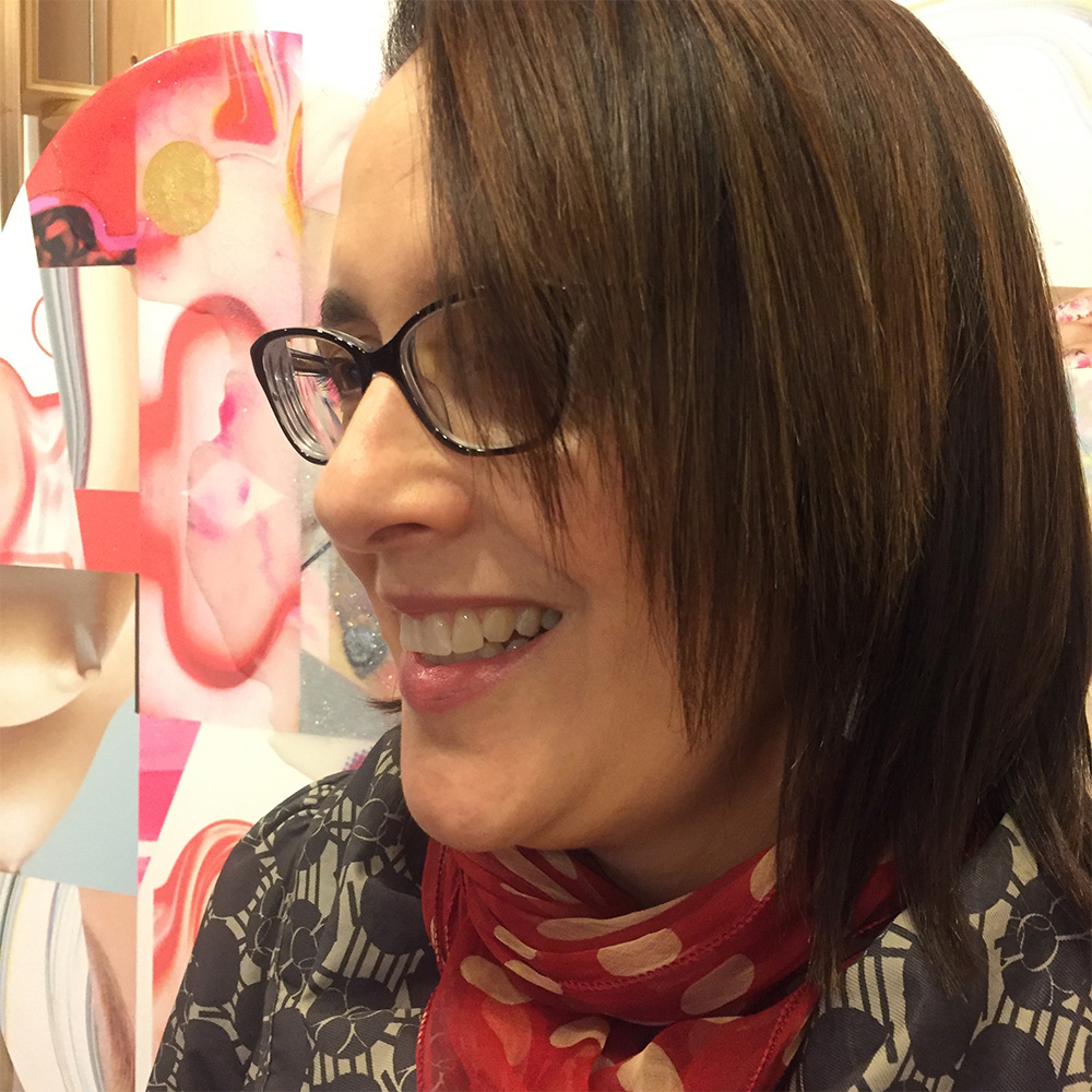 Woman with short brown hair with glasses wearing a red scarf.