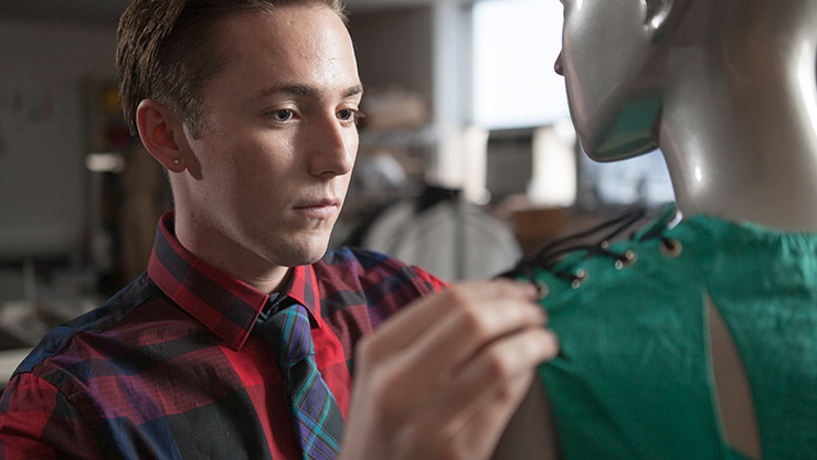 Young man wearing a red button up adjusting a green blouse on a mannequin
