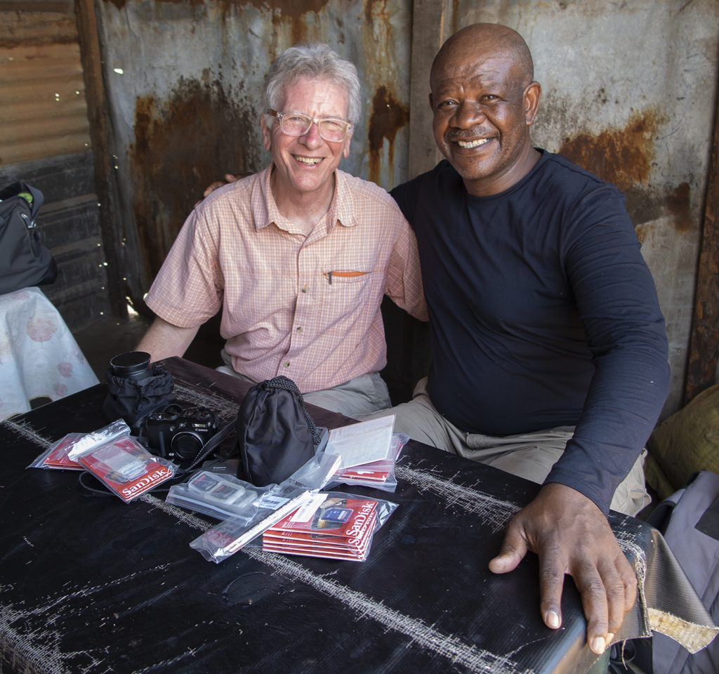 Photo of two men smiling sitting next to each other with their arms around one another with the left wearing an orange checkered shirt and grey pants and glasses and the right wearing a navy shirt and grey pants