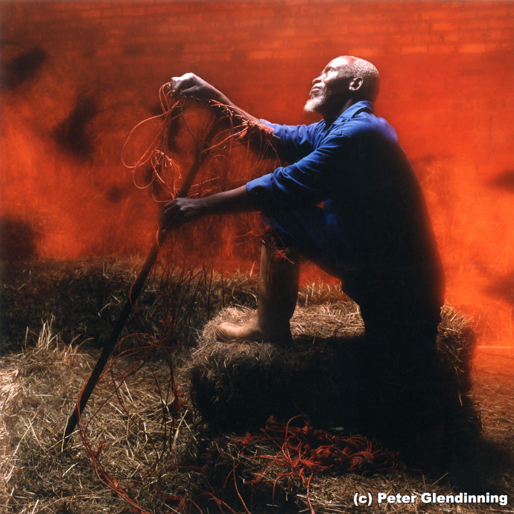 Portrait of a man with one leg up on a stack of hay holding a rake in front of a red background with brick