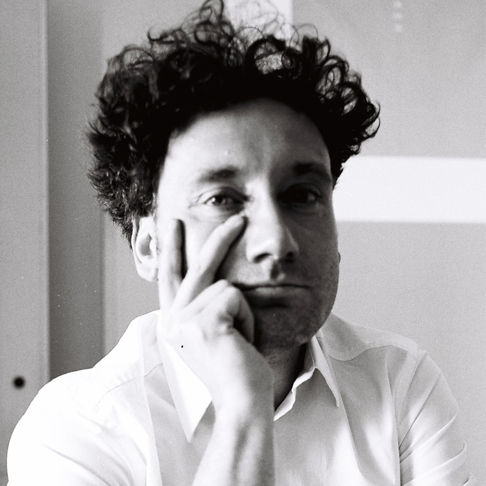 A black and white portrait of a man with curly black hair with his hand on his cheek.