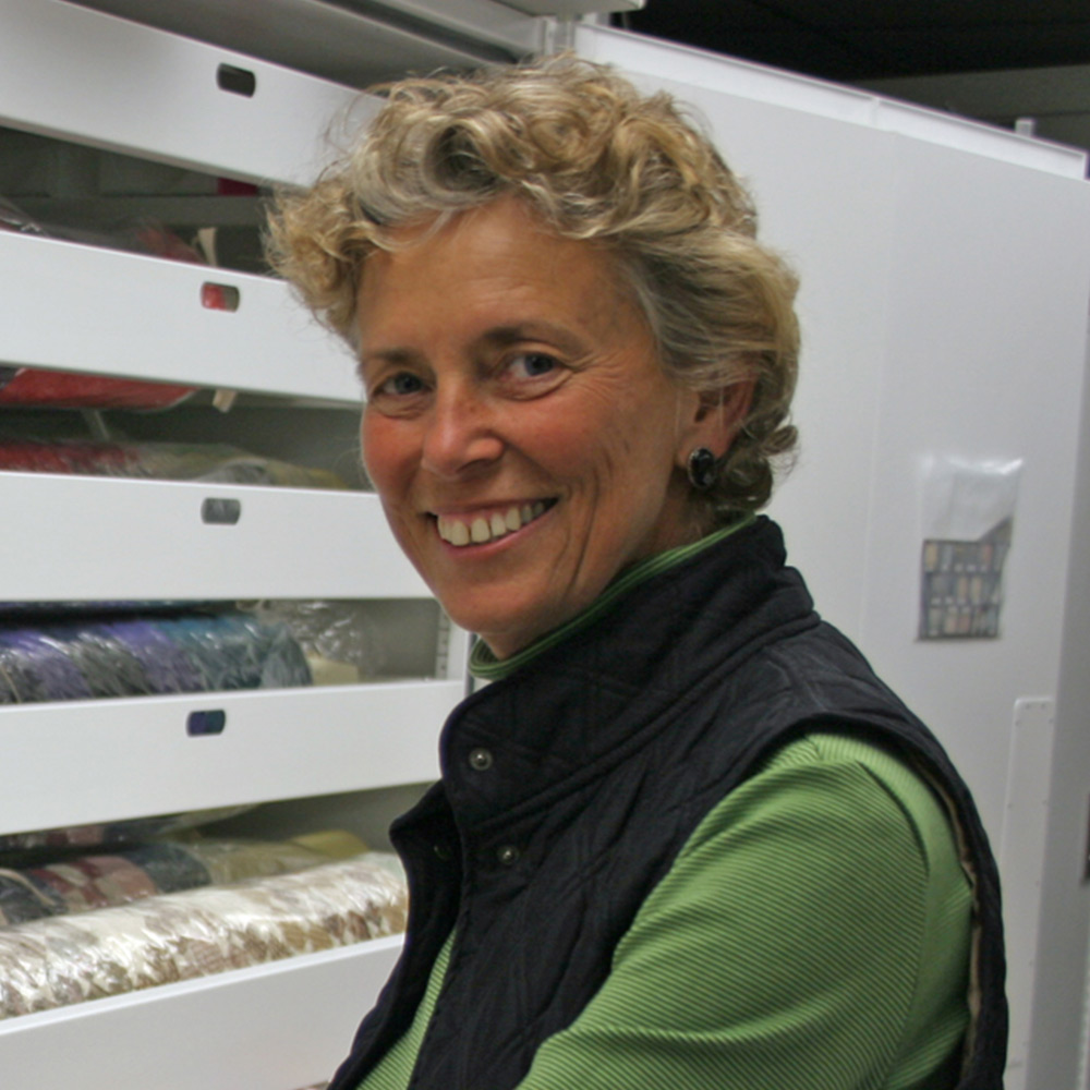 Smiling Woman with curly short hair, with a green shirt on with a black vest over it.