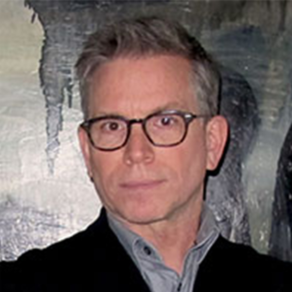 Middle aged man with short grey hair, wearing black framed glasses.