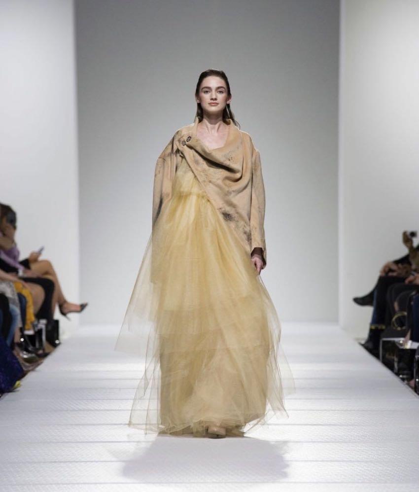 Photo of person walking down a runway wearing a long yellow dress