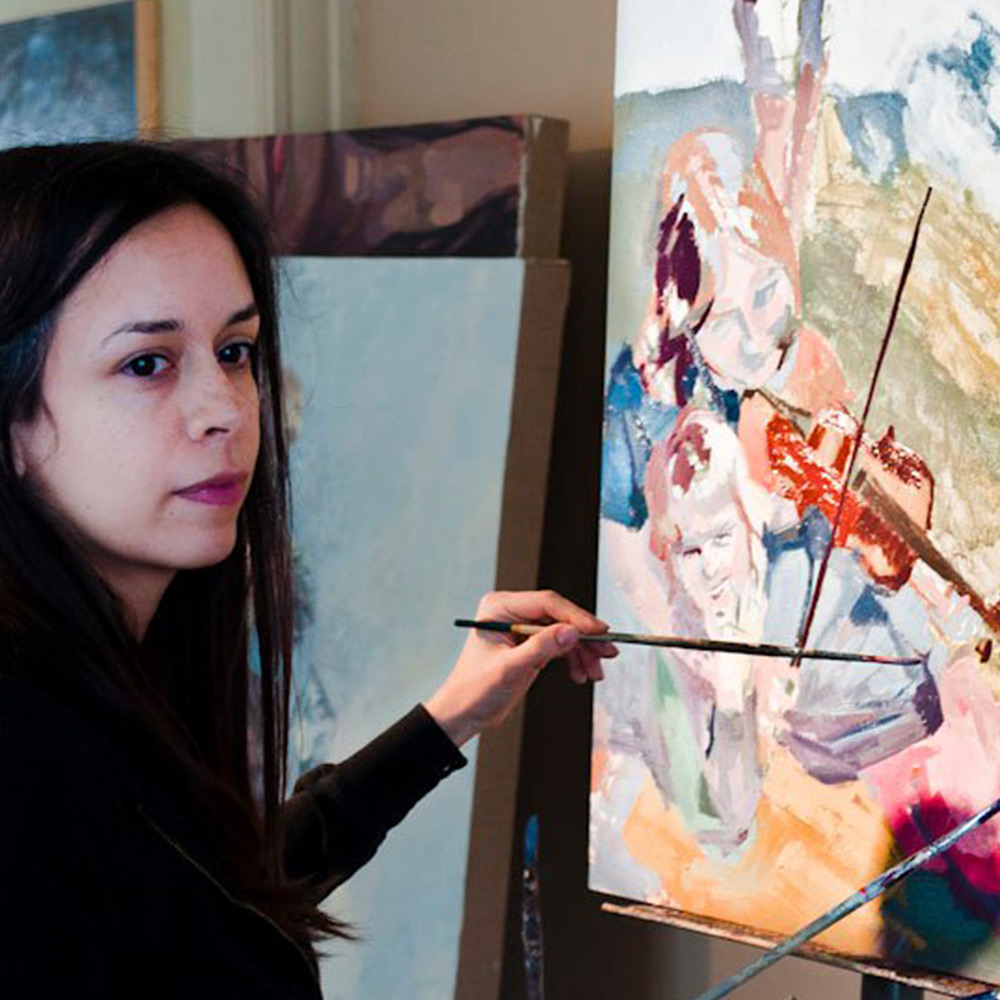 Woman with long hair in left of frame painting.