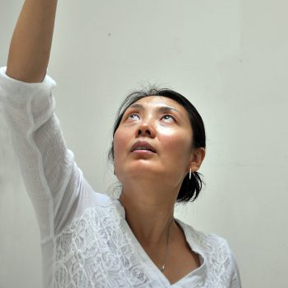 Woman with black hair pulled back. She is looking upwards with her arm outstretched up.