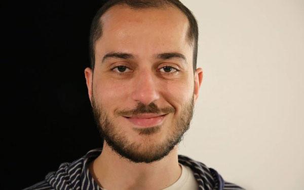 headshot of man with facial hair smiling at camera