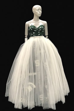 Dress on a mannequin. The bottom is white toole and the top is a green and white pattern