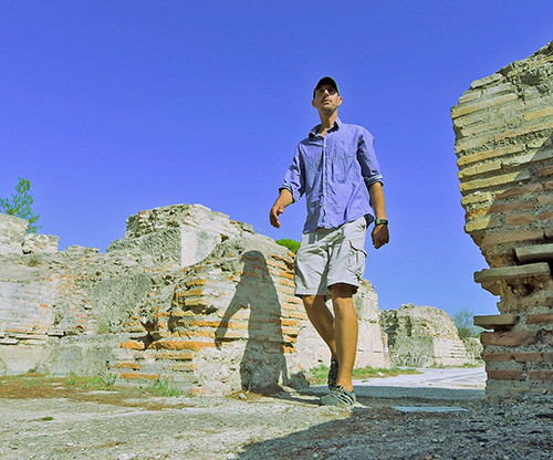 man in shorts and button down walking through rock ruins