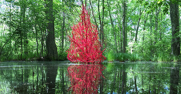 Red art installation shaped as a tree in the middle of a pond