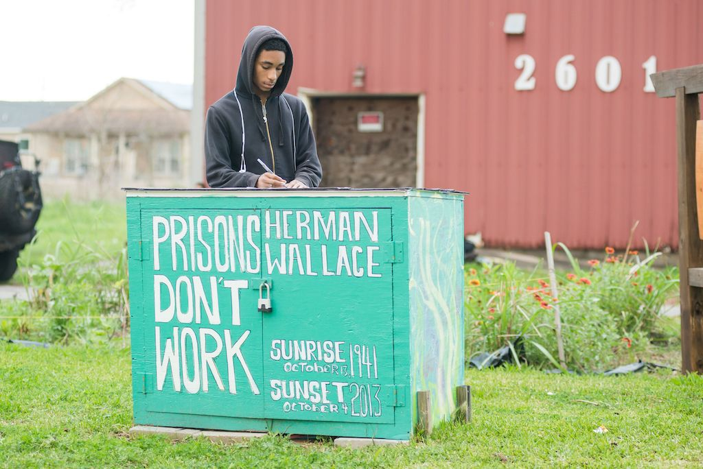 "man wearing a black hoodie is standing behind a teal wooden box that says ""prisons don't work' in white letters."