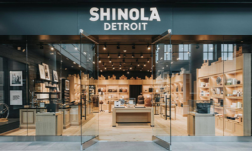 Storefront of Shinola Detroit, glass windows with wood lining the inisde of the store