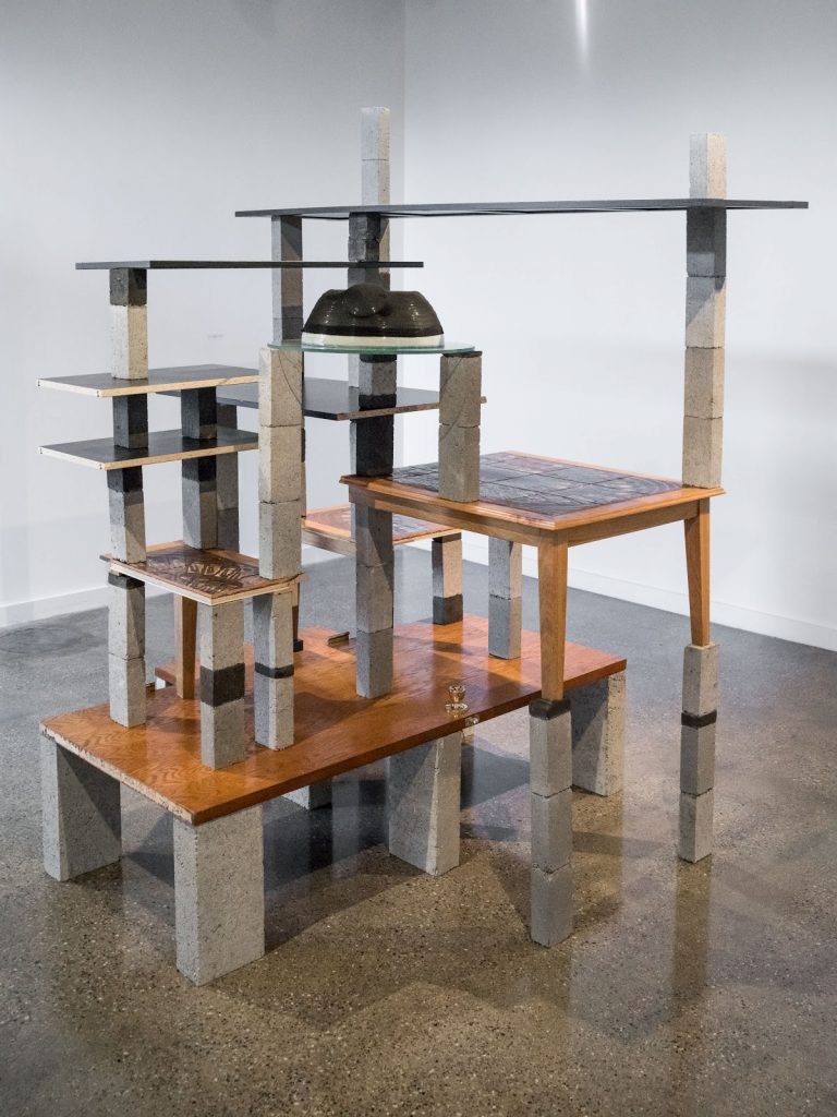 A brick and wood sculpture of tables