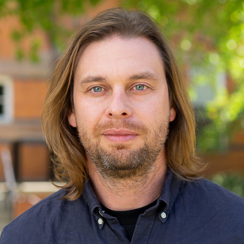 Portrait of man with long dirty blonde hair and light beard, wearing a navy button up shirt