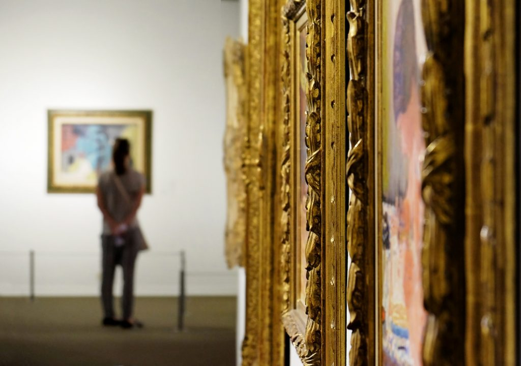 museum with paintings in intricate gold frames