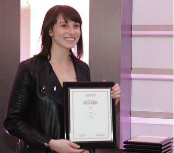 Smiling woman with black hair is holding an award