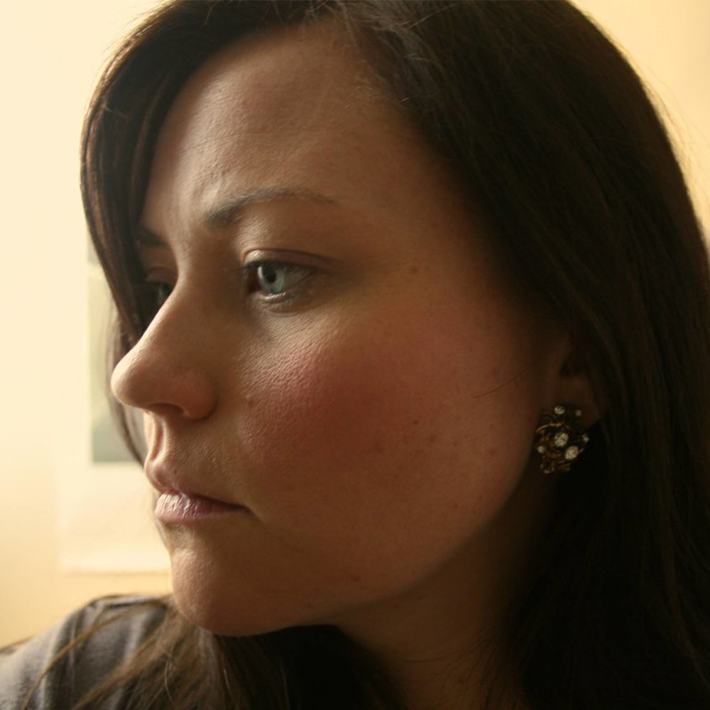 Left profile of woman with brown hair and blue eyes and an intricate earring