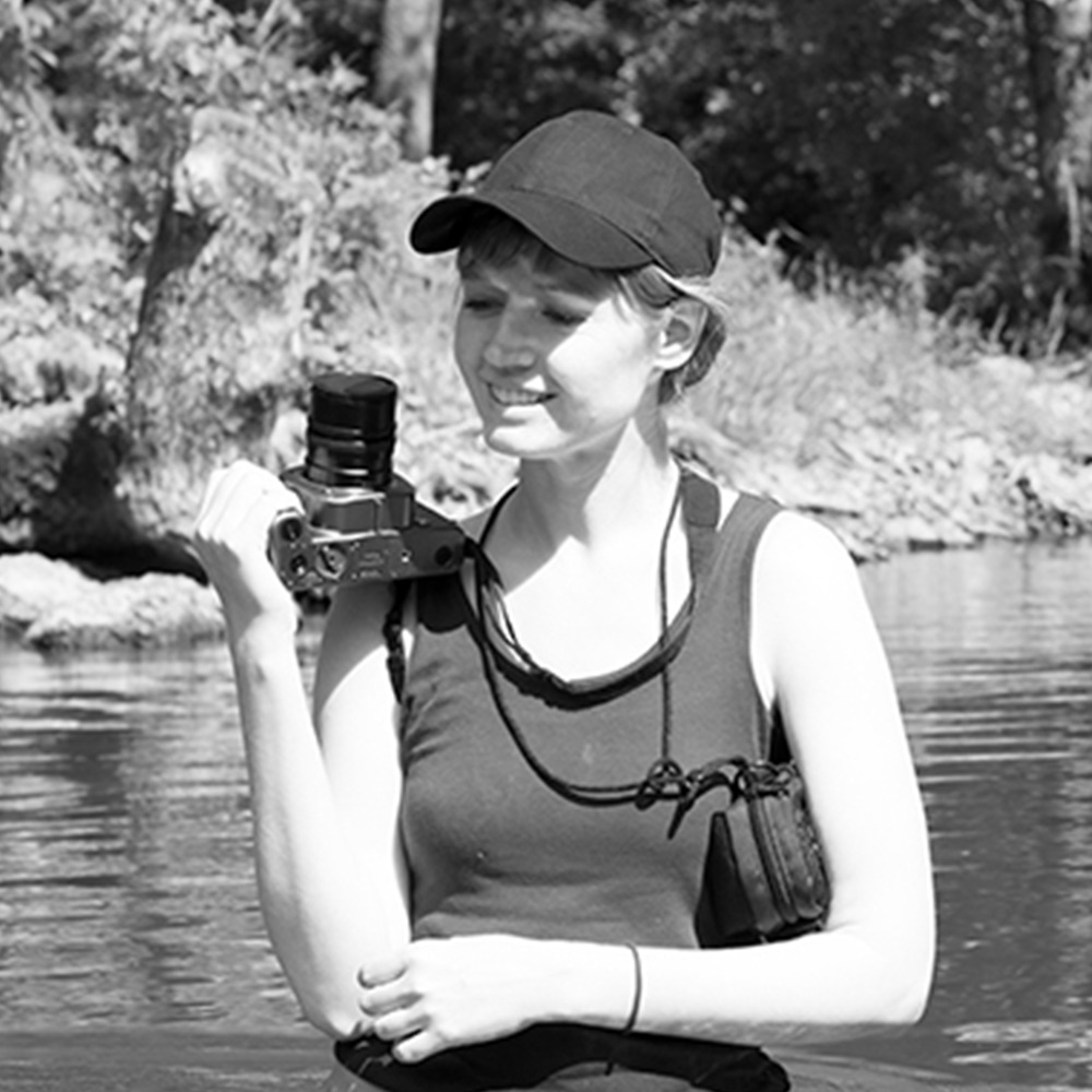 Young woman with baseball cap and camera in right hand, standing in a river