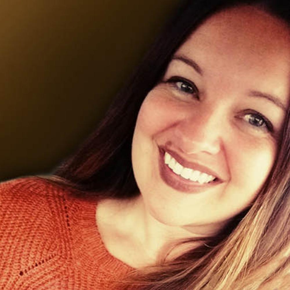 Selfie of woman with brown hair wearing an orange shirt