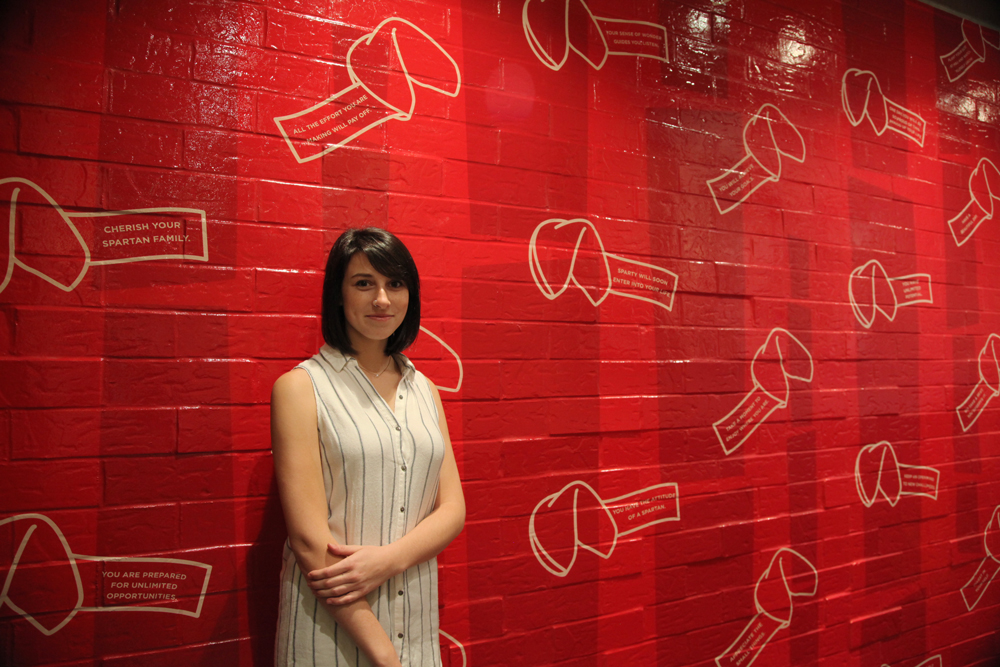 Woman with brown hair standing in front of a red wall with fortune cookies painted on it.