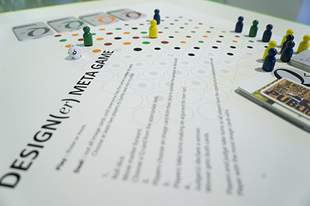 """""""Deisgn(er) Meta Game"""" poster laying on a table. There are game pieces laying on the poster"""