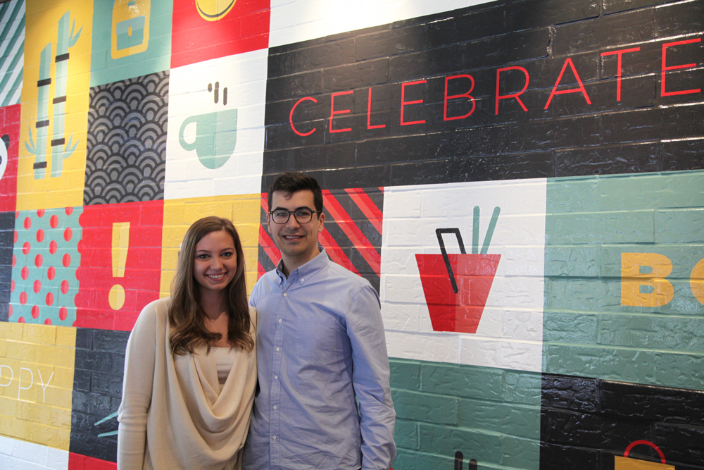 A woman (left) standing next to a man (right). They are standing in front of a colorfully painted wall.