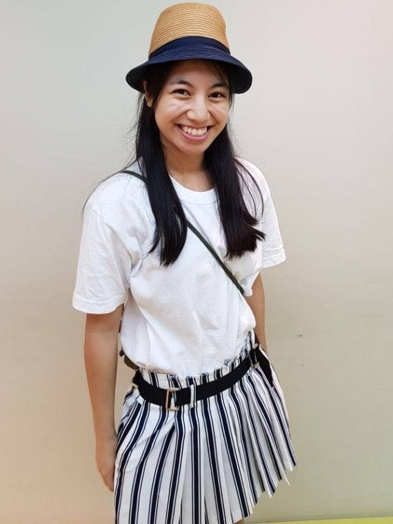 women wearing a hat and white short and stripped shorts smiling at the camera