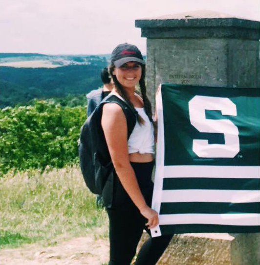 a girl with her hair braided wearing a hat a white tank black leggings and a backpack holding an MSU flag