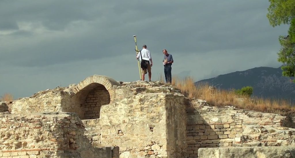 two people stand on the top of a hill
