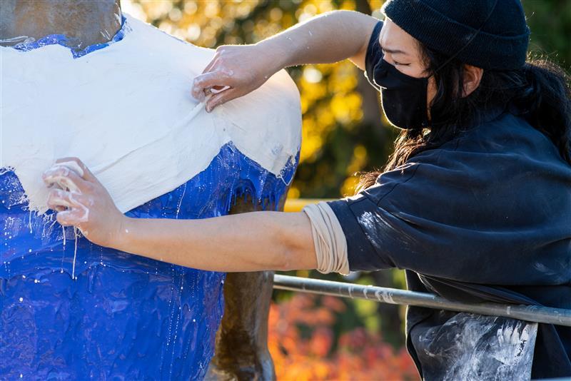 a person using papier mâché on a statue