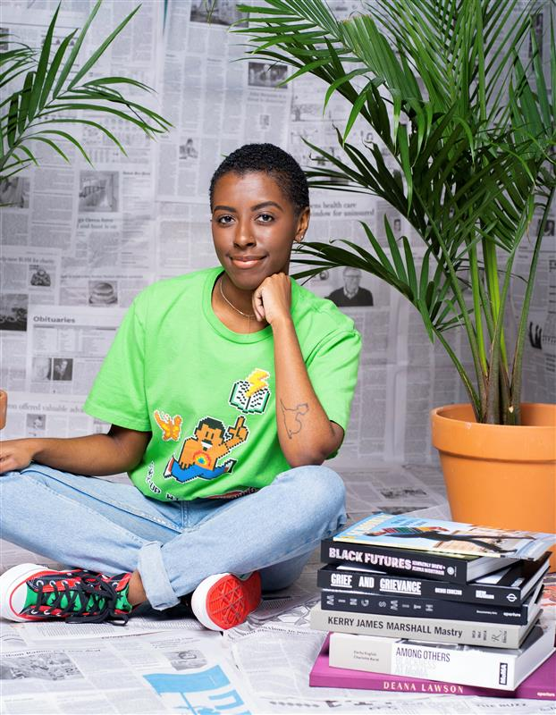 a person with short hair wearing a green shirt with blue jeans sitting with a stack of books next to them