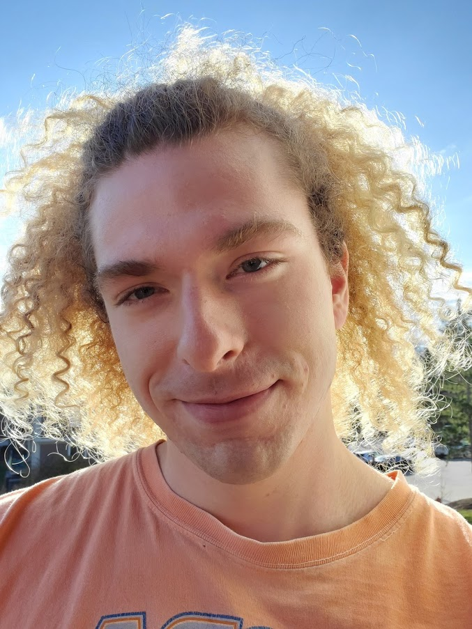 a headshot of a man with curly blonde hair wearing a t-shirt