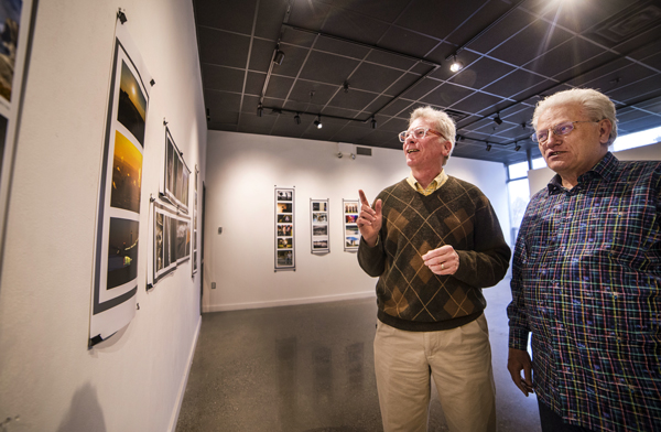Photo of two men standing side by side in an art gallery. The man on the left is pointing at a photo on the wall.
