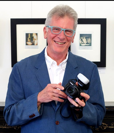 A smiling man with gray hair wearing light blue glasses and holding a camera. Behind him are two framed photos.