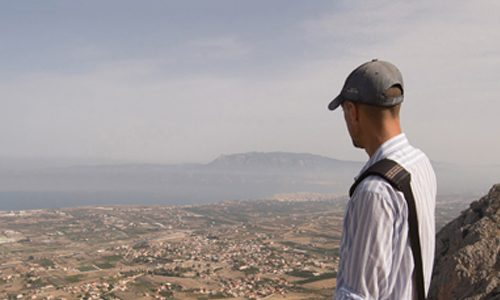 man with hat on looking from a high vantage point at a rural, desert city in Greece